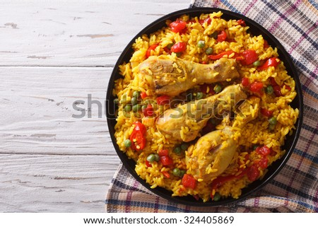 Spanish paella with chicken and vegetables on a plate. horizontal view from above