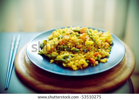 Spanish paella with seafood in a blue dish (shallow DOF) - stock photo