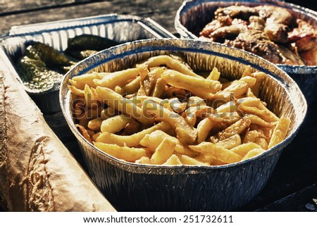 Spanish picnic set with bread, french fries, green peppers and chicken in aluminum foil tray - stock photo