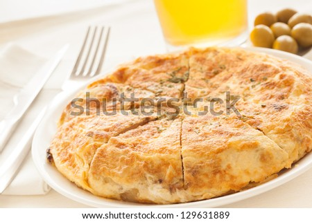 "Spanish potato omelet called ""Tortilla de Patatas"" with beer and olives, ready to eat. - stock photo"