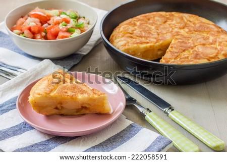 spanish potato omelette and a bowl of tomato salad - stock photo