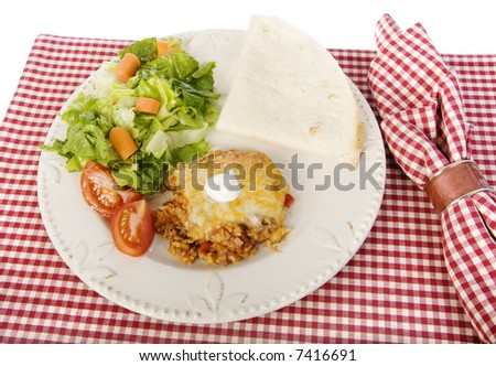 Spanish rice dinner with tossed salad and tortilla on red and white checkered placemat isolated on white background - stock photo
