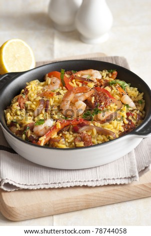 Spanish rice with king prawns and chorizo in a pan - stock photo