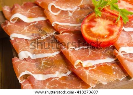 Spanish sliced serrano ham with tomato - stock photo