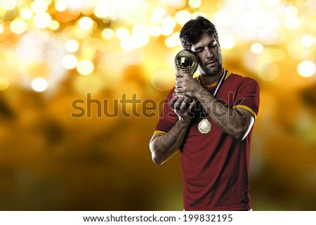 Spanish soccer player, celebrating the championship with a trophy in his hand. On a yellow lights background.