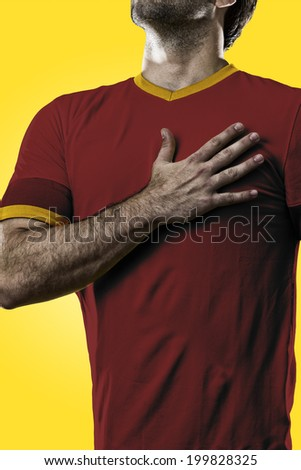 Spanish soccer player, listening to the national anthem with his hand on his chest. On a yellow background.