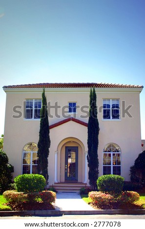 spanish style home with tall trees at entrance - stock photo