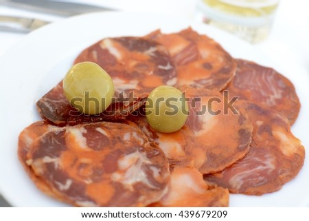 Spanish style tapas, chorizo and olives served on a white plate  - stock photo