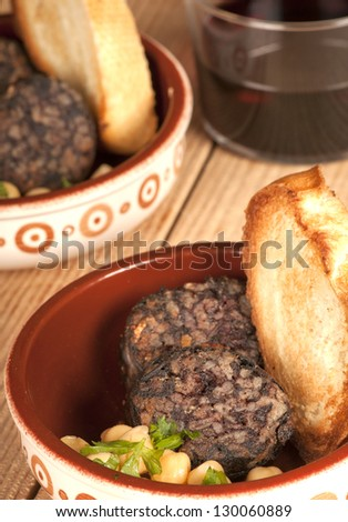 Spanish tapa morcilla, black pudding, with chick peas and toast in a rustic dish with red wine - stock photo