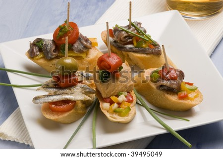 Spanish tapas. Montaditos. Bread slices mounted with tuna, anchovies, peppers and olives. Typical appetizer. - stock photo