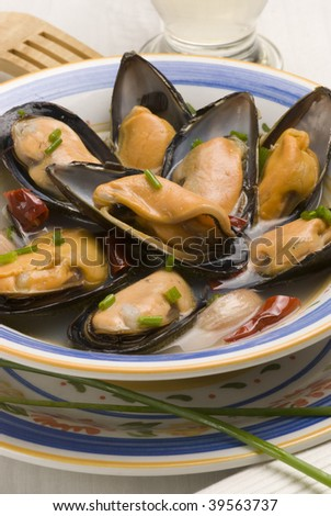 Spanish tapas.Mussels in white wine and garlic sauce. Ceramic plate. Typical appetizer. Closeup. - stock photo