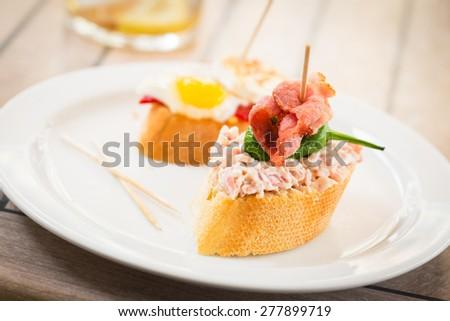 Spanish tapas on white plate. - stock photo