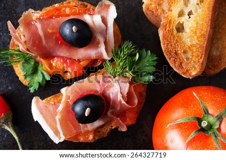 Spanish tapas with jamon on a black background with tomato and baguette. Top view - stock photo