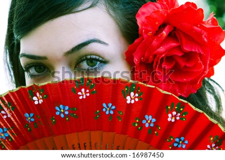 Spanish woman behind traditional fan. - stock photo