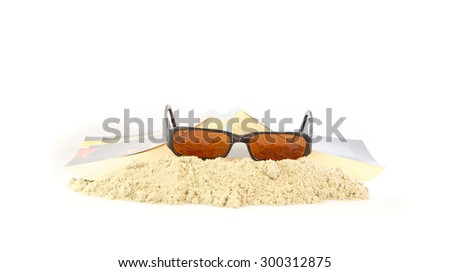 Spare time on the beach reading a good novel and sunglasses - stock photo