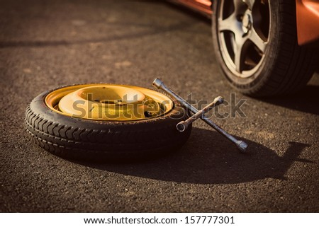 Spare wheel of a car with tool - stock photo