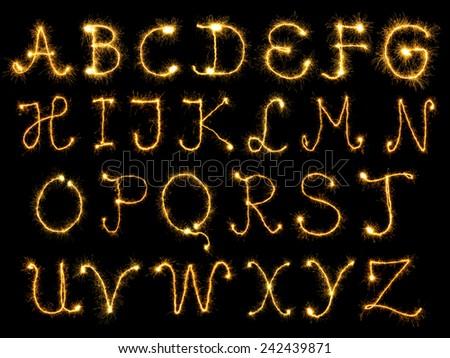 Spark alphabet over black background - stock photo