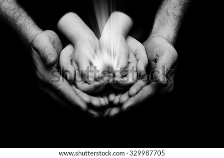 Spark of hope in a child hands who holding by parents hands on dark background. The light of faith.