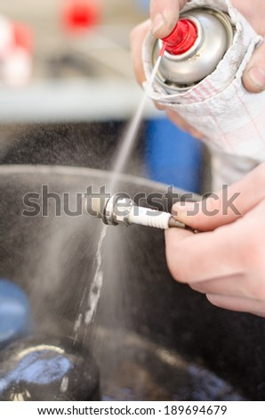 Spark plug cleaning in repair shop. - stock photo