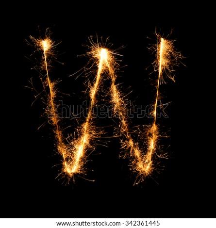 Sparkler firework light alphabet W at night background - stock photo