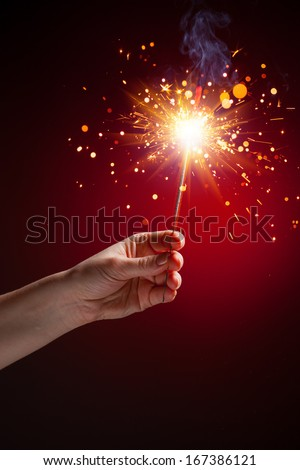 sparkler in hand, close-up view, red background - stock photo