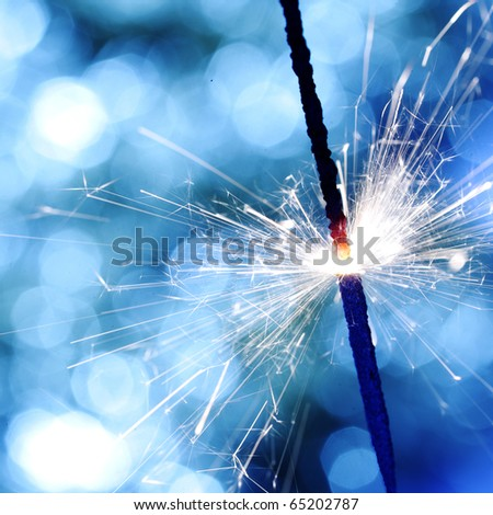 sparkler on blue - stock photo