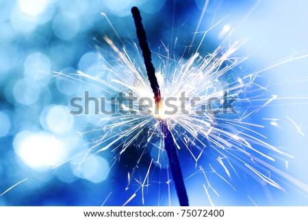 sparkler on blue bokeh background - stock photo