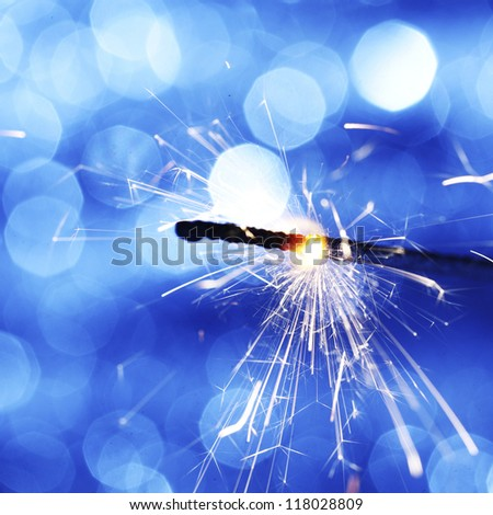 sparkler on blue bokeh background macro close up - stock photo