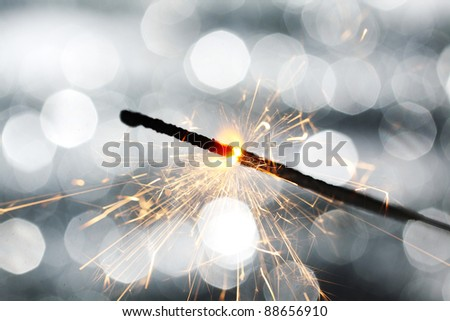 sparkler on silver bokeh background macro close up - stock photo