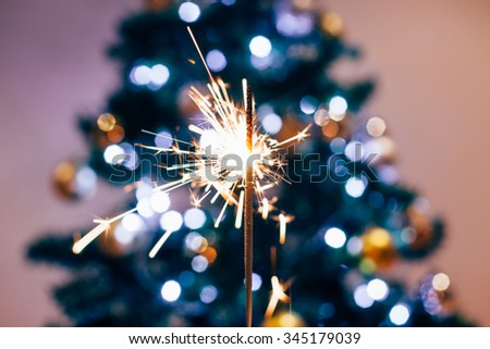 Sparkler with Christmas tree glitter in background - stock photo
