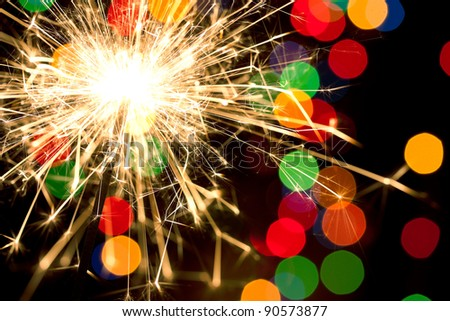 Sparklers and background with colorful bokeh - stock photo