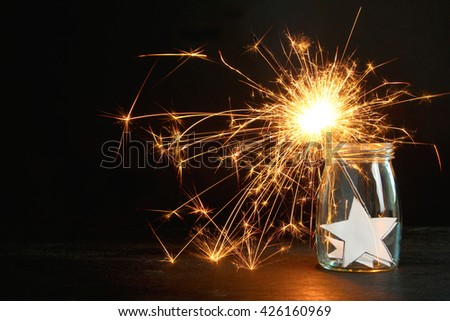 sparklers in a glass jar with a star on a wooden table - stock photo
