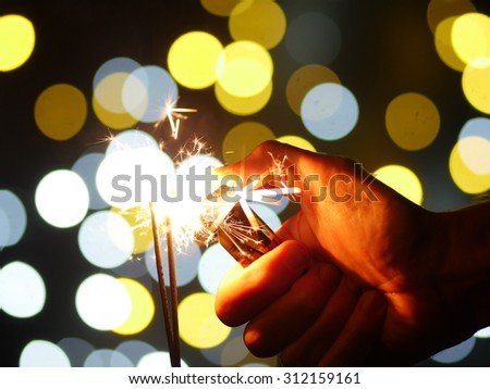 sparklers on new year's eve with bokeh background - stock photo