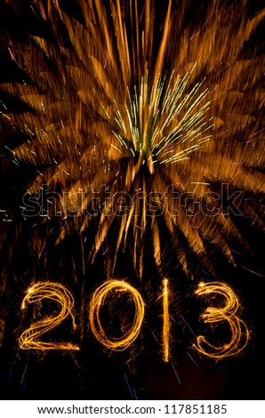Sparklers write 2013 against gold fireworks blast for New Year - stock photo