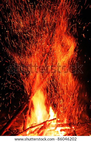 Sparkling campfire with black background - stock photo
