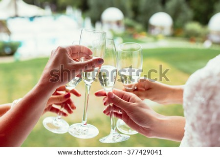 sparkling champagne glasses in girls hands on wedding day - stock photo