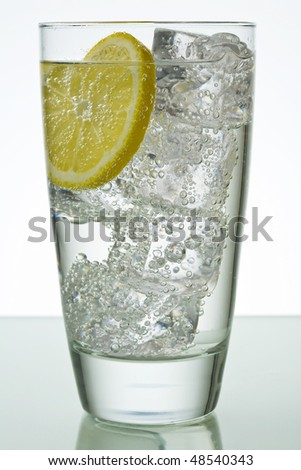 Sparkling drink in glass with ice cubes and lemon slice - stock photo