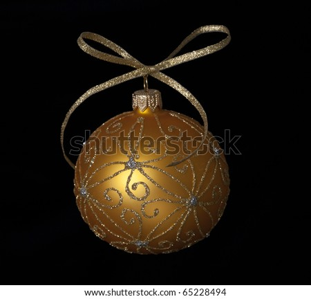 Sparkling gold christmas bauble with ribbon isolated on black, a lot of copyspace available - stock photo