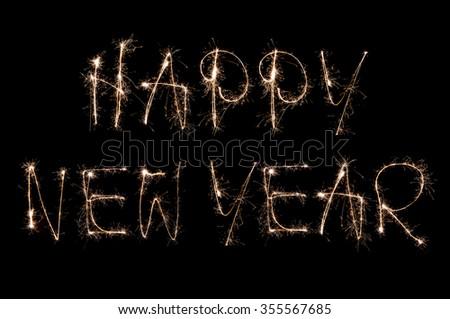 Sparkling happy new year handwritten text on black background - stock photo