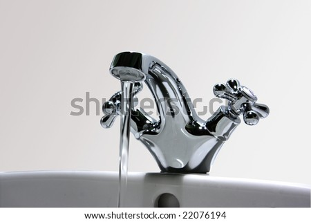 Sparkling mixer taps with running water on bathroom sink.  There is a grey faded background. - stock photo