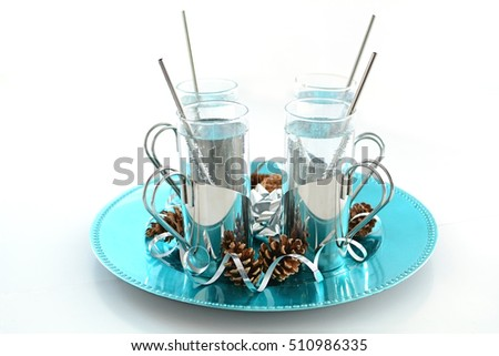 Sparkling non-caffeinated, soft drink sin silver holders on turquoise tray with festive pine cones and silver ribbon curls in horizontal format.  Shallow depth of field.