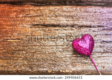Sparkling pink heart on gradient wooden background for Valentines Day - stock photo