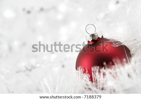 Sparkling snowy tinsel and Red christmas bauble. Selective focus
