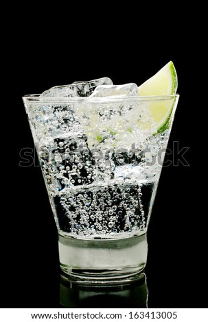 Sparkling water with ice cubes and piece of lime in old fashion glass on a black background