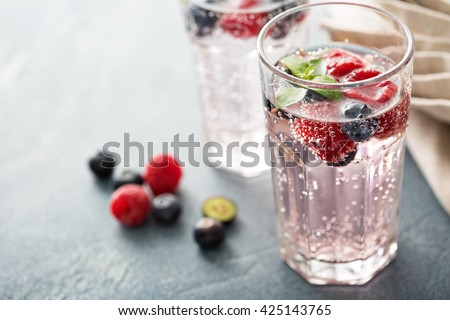 Sparkling water with mint, raspberries and blueberries - stock photo