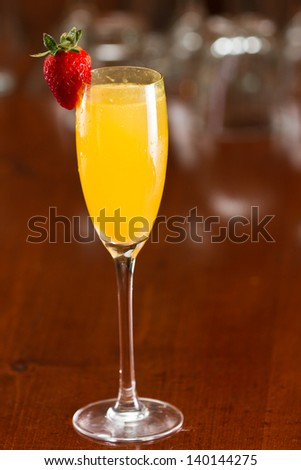 sparkling wine served in a flute with fresh orange juice garnished with a red strawberry on a out of focus bar top - stock photo