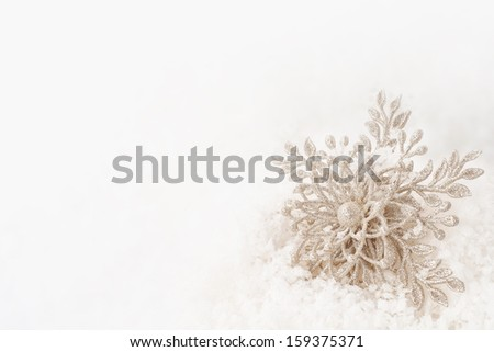 Sparkly Winter or Christmas or New Years Snowflake Ornament in Snow with Background Room or Space for Copy, your Words or Text  - stock photo