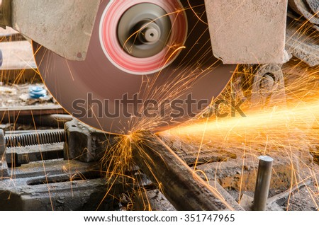 Sparks fire while cutting steel in manufacturing factory - stock photo