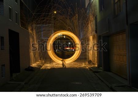 Sparks Flying off Burning Steel Wool in Alleyway - stock photo