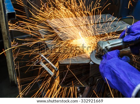 Sparks motion while grinding iron in factory - stock photo
